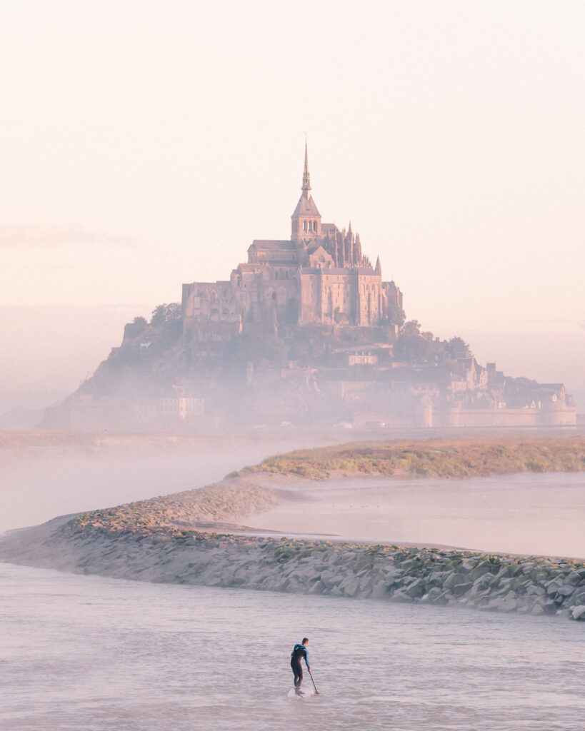 Surfer on River Approaching Mont Saint Michel