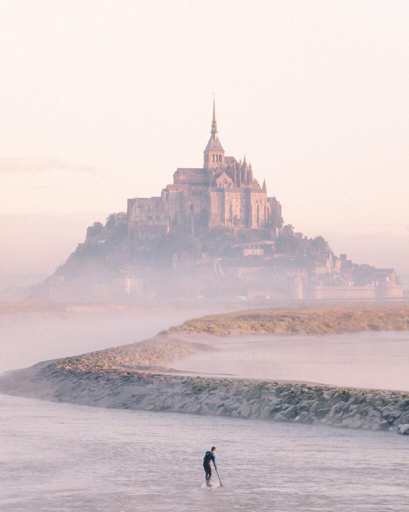 Surfer on River Approaching Mont Saint Michel