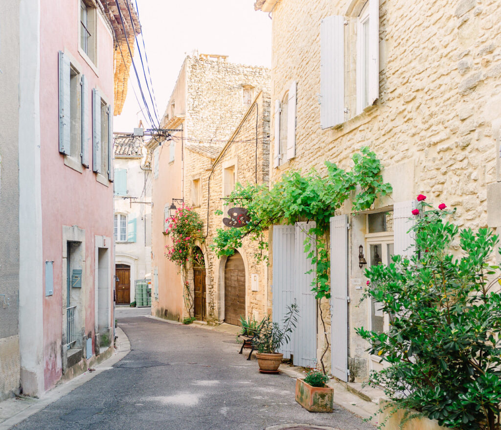 Pretty street in Provence with pastel buildings and doors covered with flowers.