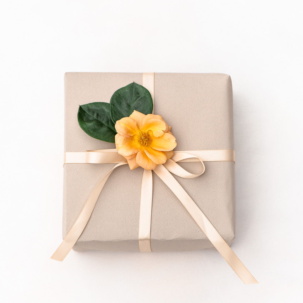 Gift wrapping with recyclable paper, reusable ribbon and flowers