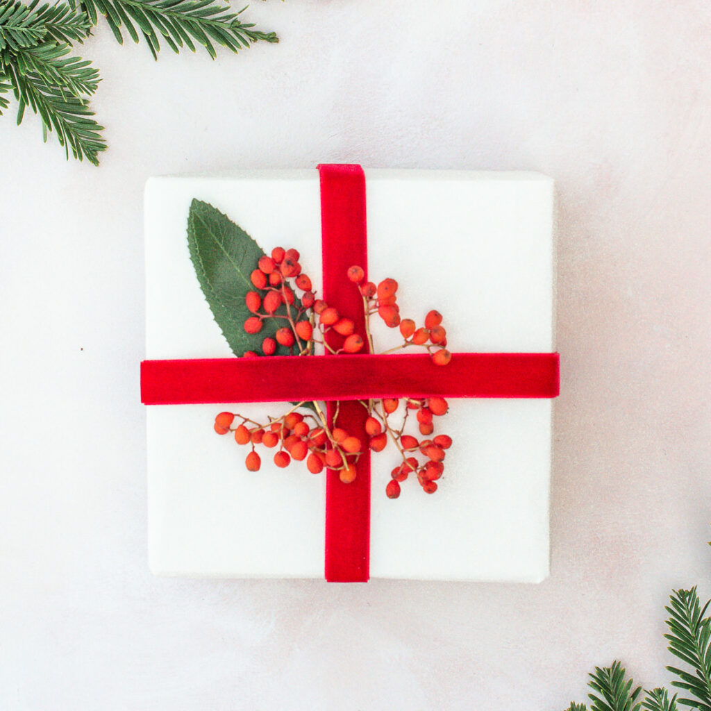 Gift wrapping with recyclable paper and natural elements.