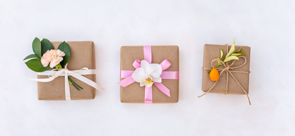 Gifts wrapped with kraft paper, flowers and twine.