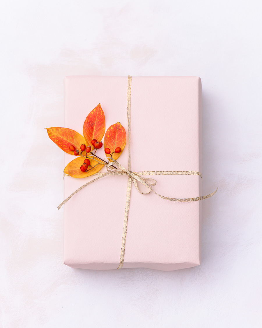 Gift wrapped with leaves and red berries
