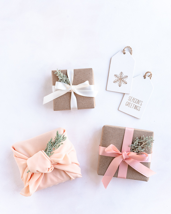 Eco friendly Christmas gift wrapping with recyclable craft paper, reusable ribbons, leaves and fabric