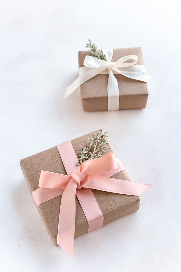 Eco friendly Christmas gift wrapping with recyclable craft paper, reusable ribbons and leaves