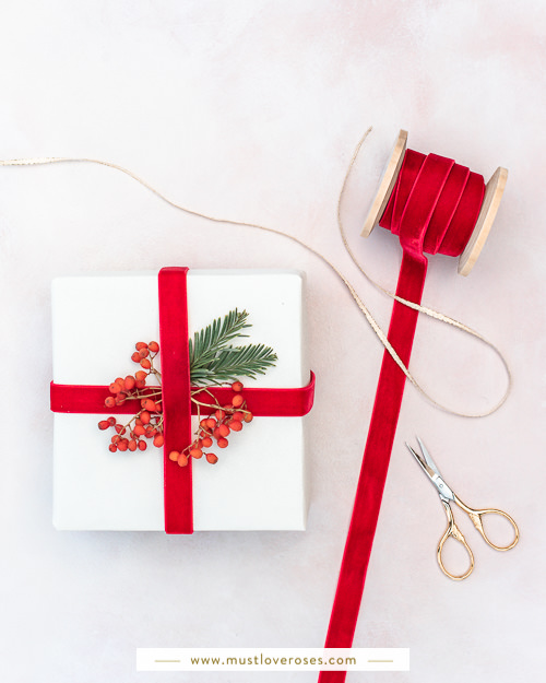 Gift wrapped with re-usable ribbon and decorated with berries